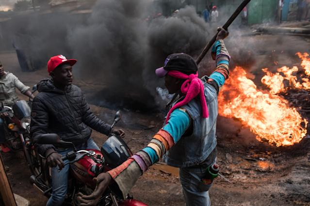 <p>A man stops motorcycles in front of a burning roadblock lit in protest for opposition presidential candidate Raila Odinga, in the Kibera slum, on Oct. 25, 2017 in Nairobi, Kenya. (Photo: Andrew Renneisen/Getty Images) </p>