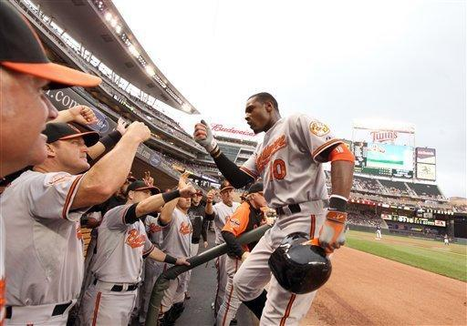 Baltimore Orioles' Adam Jones (10) is congratulated by teammates, including Jim Thome, second from left, after hitting a two-run home run against Minnesota Twins pitcher Francisco Liriano during the first inning of a baseball game on Wednesday, July 18, 2012, in Minneapolis. (AP Photo/Genevieve Ross)
