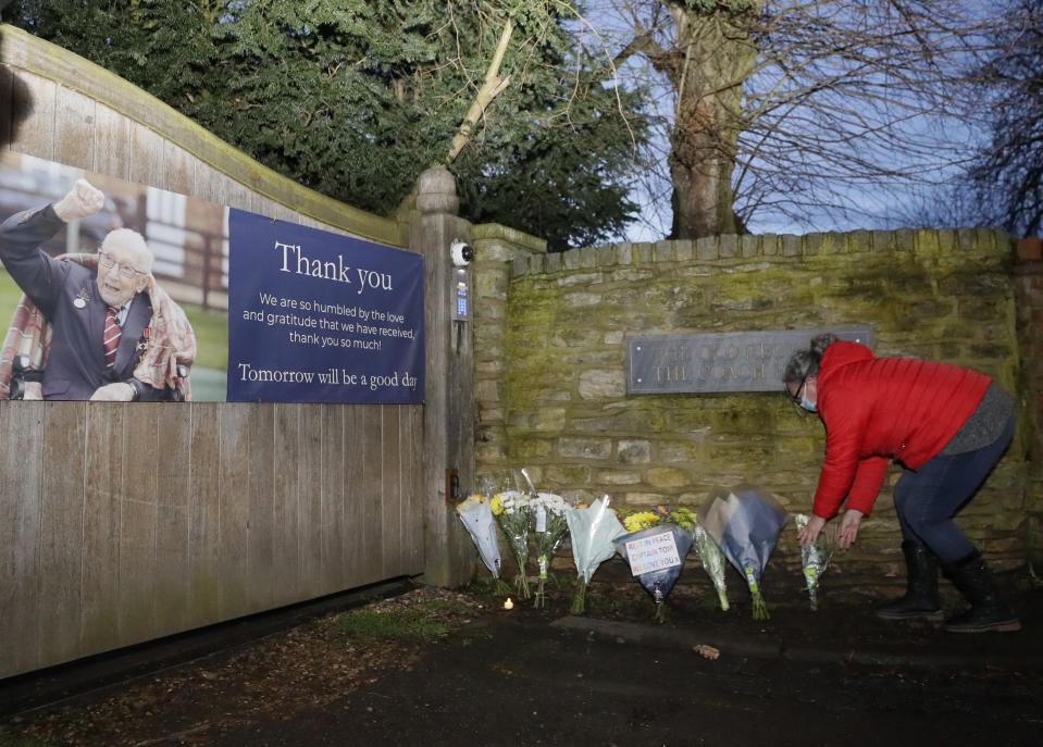 Flowers are placed near the home of Captain Tom Moore in Marston Moretaine, England, Tuesday, Feb. 2, 2021. The British World War II veteran who walked into the hearts of a nation in lockdown as he shuffled up and down his garden to raise money for health care workers has died after testing positive for COVID-19. Capt. Tom Moore was 100-years-old. (AP Photo/Kirsty Wigglesworth)
