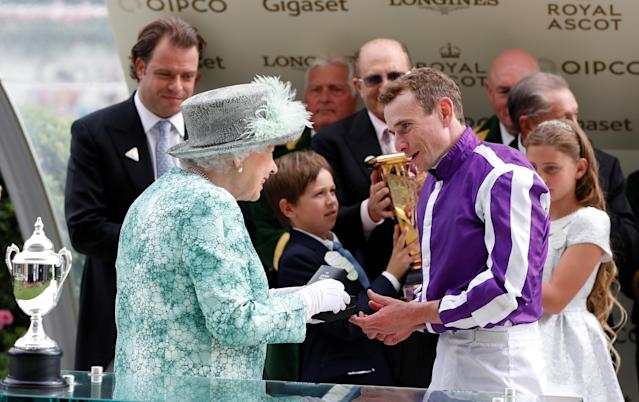 Horse Racing - Royal Ascot - Ascot Racecourse, Ascot, Britain - June 23, 2018 Britain's Queen Elizabeth presents a trophy for the 4.20 Diamond Jubilee Stakes to Ryan Moore, who rode the winner Merchant Navy Action Images via Reuters/Paul Childs