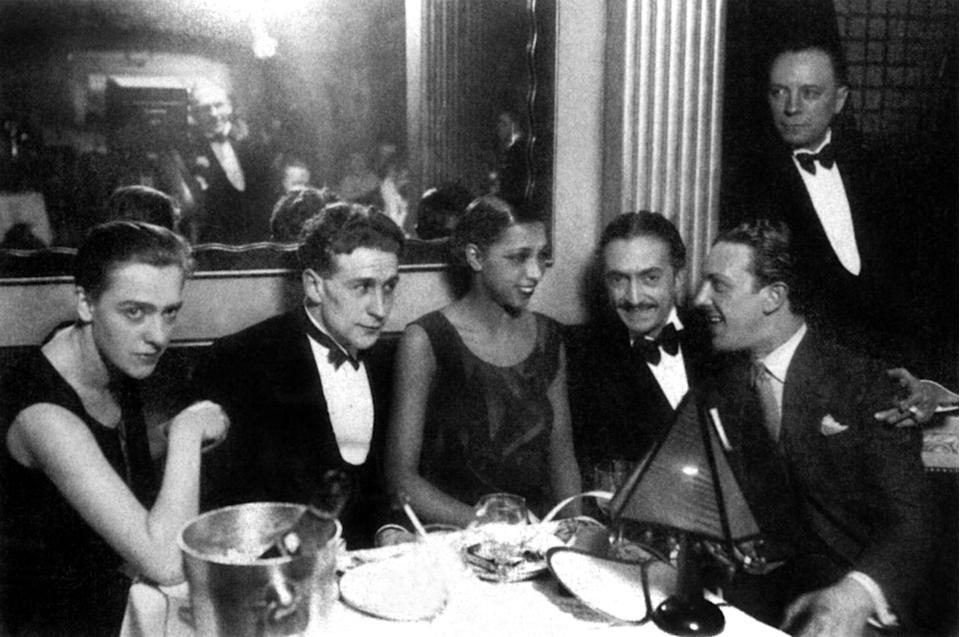 <p>Baker dines at a chic restaurant in Paris in 1928. The young performer was out to dinner with famous writer Georges Simenon, his wife, and her manager and lover, Pepito. </p>