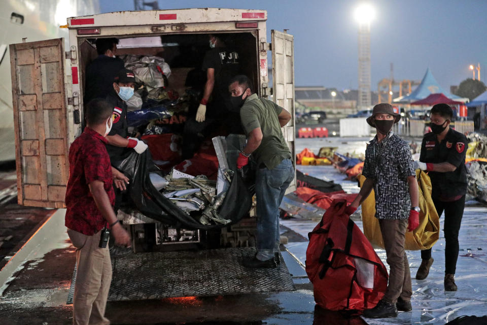 Workers load wreckage from Sriwijaya Air flight SJ-182 that crashed into the Java Sea on Jan. 9, onto a truck be transported for further investigation at Tanjung Priok Port in Jakarta, Indonesia, Thursday, Jan. 21, 2021. Indonesian authorities on Thursday ended the search for the wreckage of the plane that nose-dived into the sea, killing all of its passengers on board. (AP Photo/Dita Alangkara)