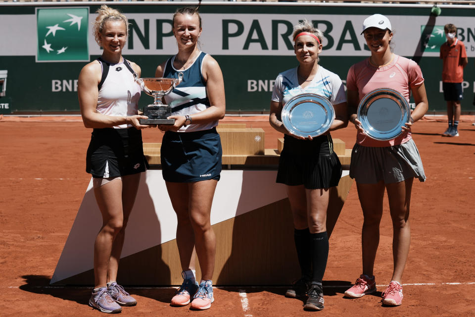 Czech Republic's Barbora Krejcikova, second left, and compatriot Katerina Siniakova, left, USA's Bethanie Mattek-Sands, second right, and Poland's Iga Swiatek hold their trophies after their women's doubles final match of the French Open tennis tournament at the Roland Garros stadium Sunday, June 13, 2021 in Paris. Czech Republic's Barbora Krejcikova playing with fellow Cezch player Katerina Siniakova, won the doubles final 6-4, 6-2. (AP Photo/Thibault Camus)