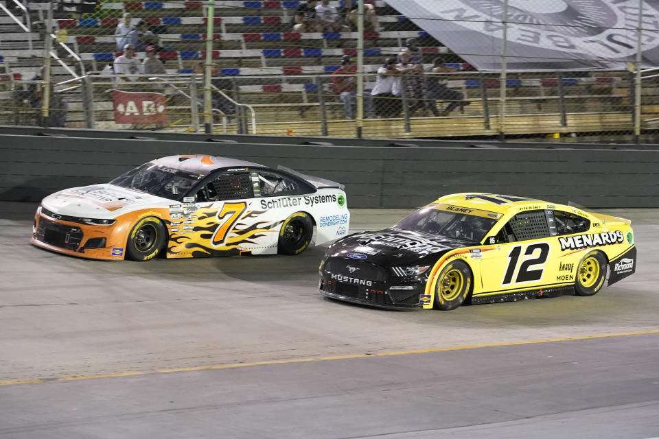 Corey LaJoie (7) and Ryan Blaney (12) come through a turn during a NASCAR Cup Series auto race at Bristol Motor Speedway Saturday, Sept. 18, 2021, in Bristol, Tenn. (AP Photo/Mark Humphrey)