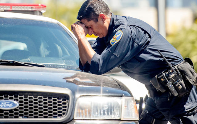 <p>A police officer reacts at the scene where a gunman shot and killed multiple people including himself at a UPS facility in San Francisco, California on June 14, 2017. (Josh Edelson/AFP/Getty Images) </p>