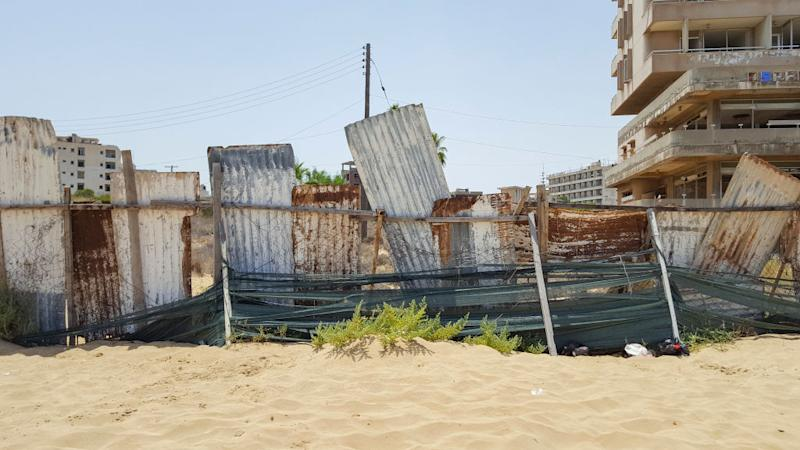 Pictured is a metal barricade and abandoned hotel buildings in Varosha.
