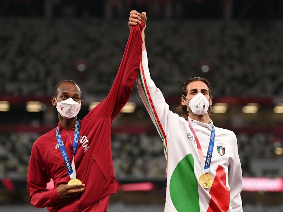 Qatar's Mutaz Essa Barshim and Italy's Gianmarco Tamberi hold hands while sharing a joint gold medal in the high jump.