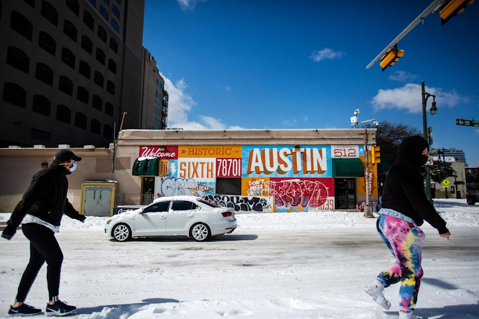 Pedestrians walk on along a snow-covered street on February 15, 2021 in Austin, Texas. (Photo by Montinique Monroe/Getty Images)