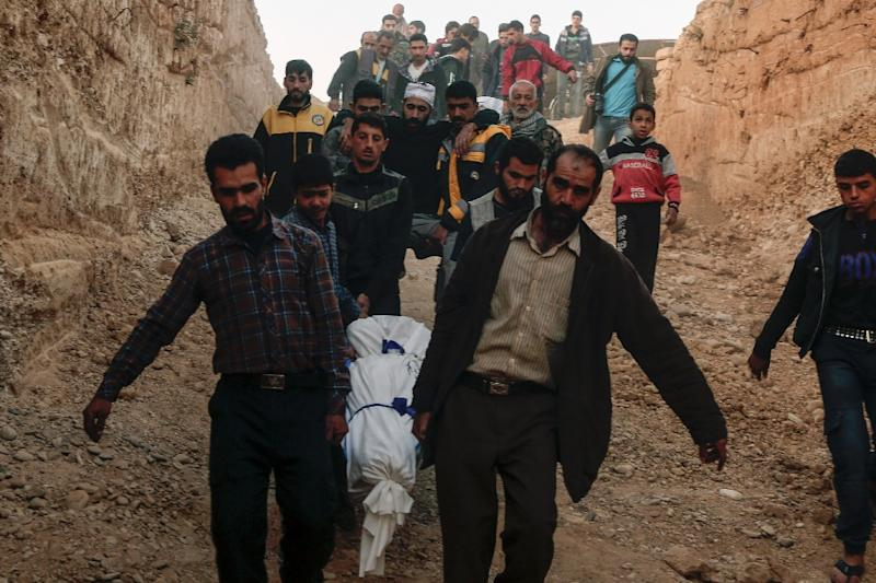 Syrians carry for burial the bodies of victims who died following reported shelling by Syrian government forces in the rebel-held town of Douma in eastern Syria. The conflict has claimed over 300,000 lives