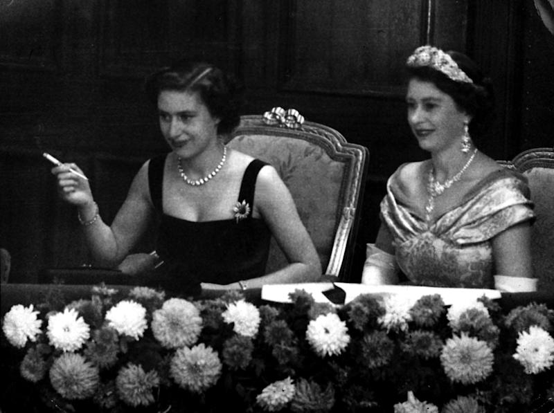 Their eyes riveted on the stage, Queen Elizabeth II, right, and her sister, Princess Margaret, smoking a cigarette, watch the Royal Variety Performance from the Royal Box at the Palladium, London. (Photo by PA Images via Getty Images)