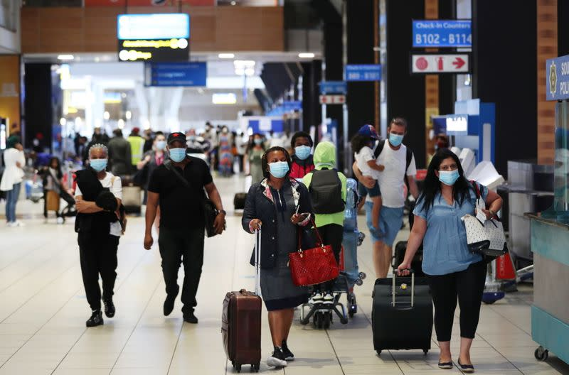 Passengers wearing protective masks walk to the check-in counters at the O.R. Tambo International Airport in Johannesburg