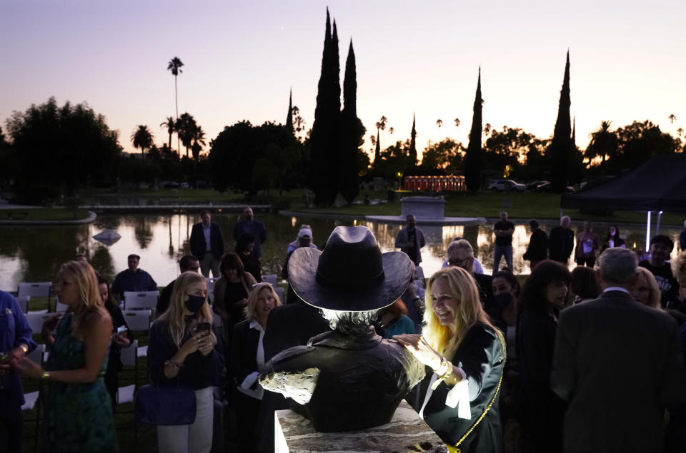 Guests gather around a newly unveiled memorial sculpture of the late actor Burt Reynolds following a ceremony at Hollywood Forever Cemetery, Monday, Sept. 20, 2021, in Los Angeles. Reynolds died in 2018 at the age of 82. (AP Photo/Chris Pizzello)