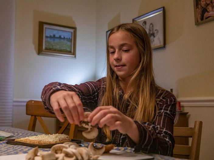 A 12 year old girl tops a pizza for dinner while working with occupational therapist Karen Dilfer, who specializes in food, in 2019.