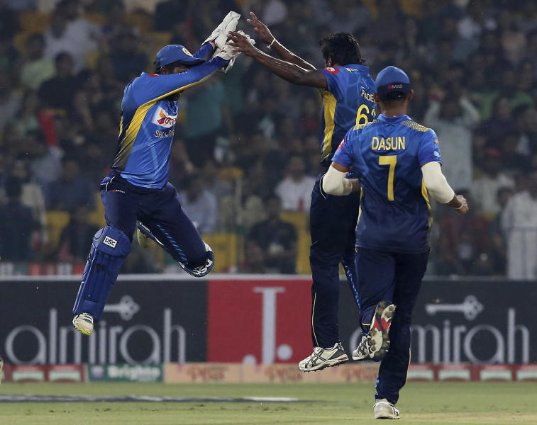 Sri Lankan pacer Nuwan Pradeep, center, celebrate with teammate after the taking the wicket of Pakistani batsman Umar Akmal during 1st Twenty20 match at Gaddafi stadium in Lahore, Pakistan, Saturday, Oct. 5, 2019. (AP Photo/K.M. Chaudary)