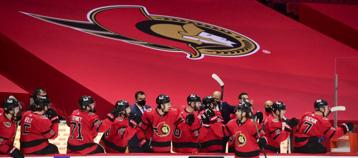 The Ottawa Senators bench celebrates a first period goal by teammate Colin White during the first period of an NHL hockey game against the Montreal Canadiens in Ottawa on Saturday, Feb. 6, 2021. (Sean Kilpatrick/The Canadian Press via AP)