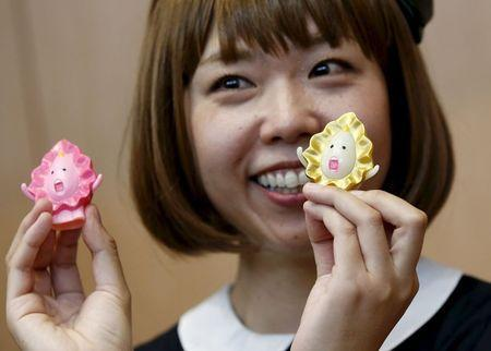 Japanese artist Megumi Igarashi, known as Rokudenashiko, holds her vagina-inspired artworks after a news conference following a court appearance in Tokyo April 15, 2015. REUTERS/Toru Hanai