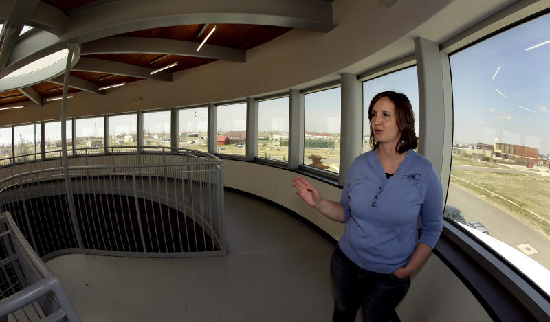 In this photo taken April, 18, 2014, museum director Stacy Barnes looks out over scattered rebuilt homes from a viewing deck at the rebuilt Big Well Museum in Greensburg, Kan. Seven years after an EF-5 tornado destroyed most of the community of 1,500, many of the town's destroyed civic buildings have been rebuilt but a rebound in population is slow in coming. (AP Photo/Charlie Riedel)