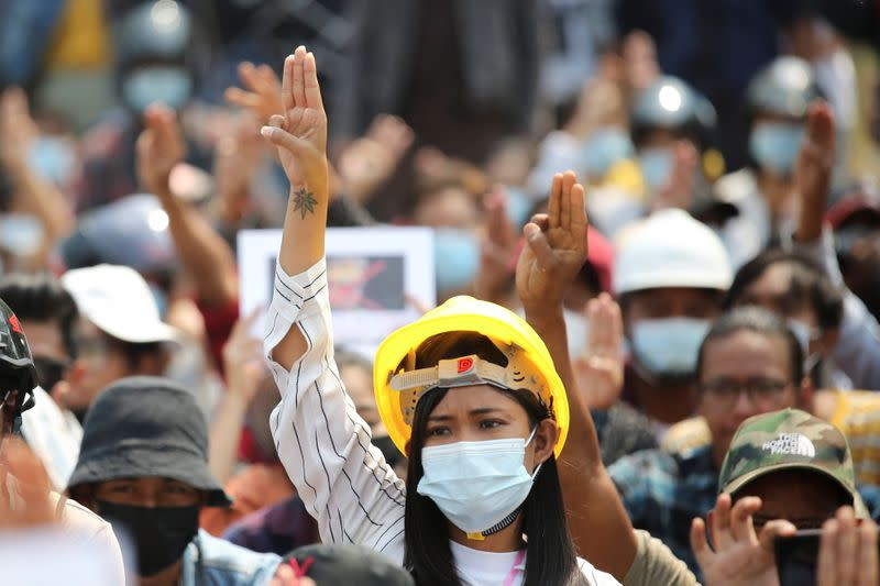 A woman shows a three-finger salute during a protest against the military coup in Naypyitaw