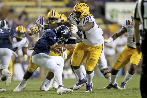 Georgia Southern quarterback Justin Tomlin (17) is wrapped up by LSU defensive end Glen Logan (97) in the third quarter of an NCAA college football game in Baton Rouge, La., Saturday, Aug. 31, 2019. (AP Photo/Michael Democker)