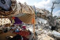 Palestinians sit in tents amid the rubble of their houses which were destroyed by Israeli air strikes