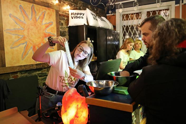 <p>Chrissy Brun looks over a cannabis menu with customers at the Natural Vibe store after legal recreational marijuana went on sale in St John's, Newfoundland and Labrador, Canada, Oct. 17, 2018. (Photo: Chris Wattie/Reuters) </p>