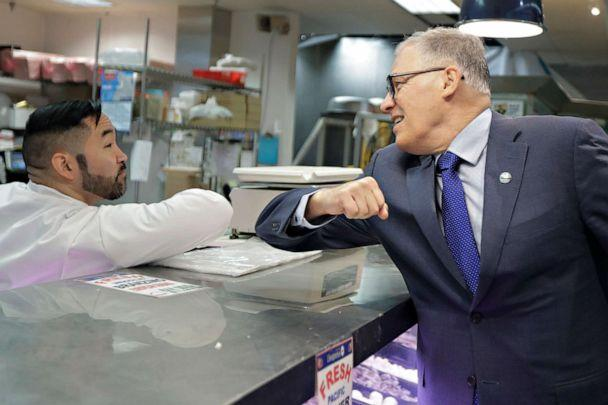 PHOTO: Washington Gov. Jay Inslee bumps elbows with a worker at the seafood counter of the Uwajimaya Asian Food and Gift Market, March 3, 2020, in Seattle's International District. (Ted S. Warren/AP)