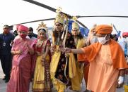 Uttar Pradesh state Governor Anandiben Patel, left, and Chief Minister Yogi Adityanath receive artists dressed as Hindu god Ram, goddess Sita and Lakshman as they alight from a helicopter on the banks of river Saryu on the eve of Diwali, the Hindu festival of lights, in Ayodhya, India, Friday, Nov. 13, 2020. Diwali will be celebrated on Saturday. (AP Photo/Rajeev Bhatt)