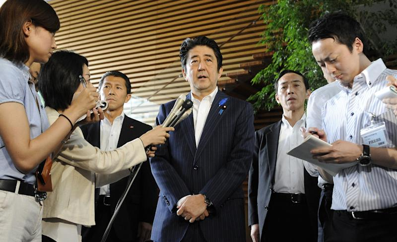 Japanese Prime Minister Shinzo Abe (C) speaks to reporters at his official residence in Tokyo on July 3, 2014