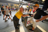 Tom Congdon, left center, a vendor at Pittsburgh sports venues for 38 years, mans his beer and water cart in the concourse at PNC Park during a baseball game between the Pittsburgh Pirates and the Atlanta Braves in Pittsburgh, Monday, July 5, 2021. It would be premature to say that the scene at major league ballparks has completely returned to normal, but there's no question this season has been a step in that direction — perhaps most crucially for the people who work there. With fans back in the stands and concessions being sold, ballpark employees have had a chance to return after the pandemic hit many of them hard. (AP Photo/Gene J. Puskar)