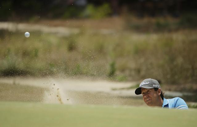 Erik Compton hits out of the bunker on the first hole during the third round of the U.S. Open golf tournament in Pinehurst, N.C., Saturday, June 14, 2014. (AP Photo/Chuck Burton)
