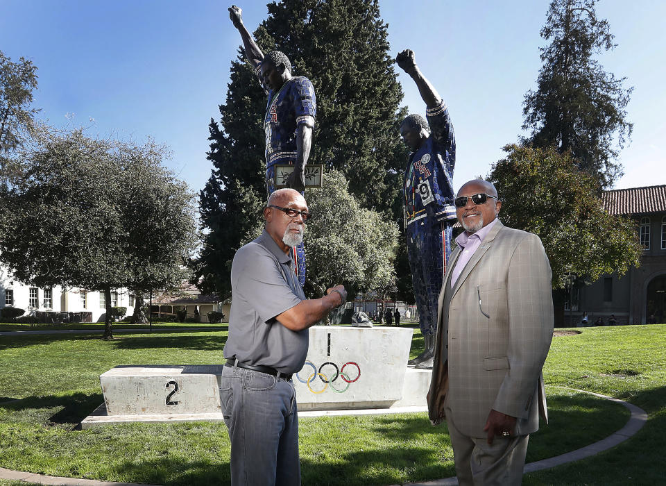 FILE - In this Oct. 17, 2018, file photo, John Carlos, left, and Tommie Smith pose for a photo in front of statue that honors their iconic, black-gloved protest at the 1968 Olympic Games, on the campus of San Jose State University in San Jose, Calif. Smith, Carlos and Gwen Berry are among the more than 150 educators, activists and athletes who signed a letter Thursday, July 22, 2021, urging the IOC not to punish participants who demonstrate at the Tokyo Games. ( (AP Photo/Tony Avelar, File)
