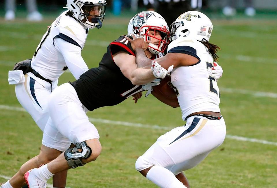 N.C. State linebacker Payton Wilson (11) tackles Georgia Tech running back Jordan Mason (27) for a loss during the Wolfpack's game against Georgia Tech at Carter-Finley Stadium in Raleigh, N.C., Saturday, Dec. 5, 2020. In the game, Wilson led the team with 11 tackles despite playing with two dislocated shoulders.