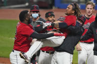 Cleveland Indians starting pitcher Carlos Carrasco, right, picks up Jose Ramirez as he celebrates with Franmil Reyes, left, after Ramirez hit a three-run home run in the tenth inning of a baseball game against the Chicago White Sox, Tuesday, Sept. 22, 2020, in Cleveland. The Indians won in ten innings. (AP Photo/Tony Dejak)