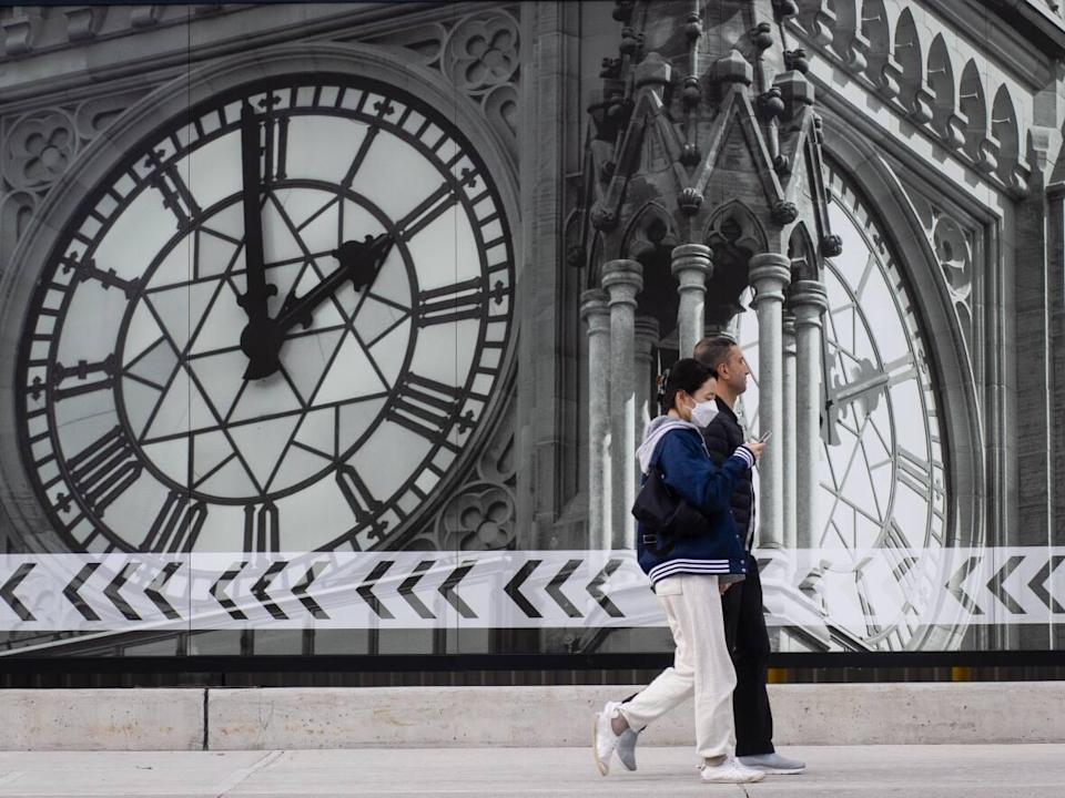 Two people, one wearing a mask, walk past a large photographic rendition of the Peace Tower installed on the Parliament Hill construction site. On Monday, health officials reported 27 new cases of COVID-19 in the nation's capital. (Trevor Pritchard/CBC - image credit)