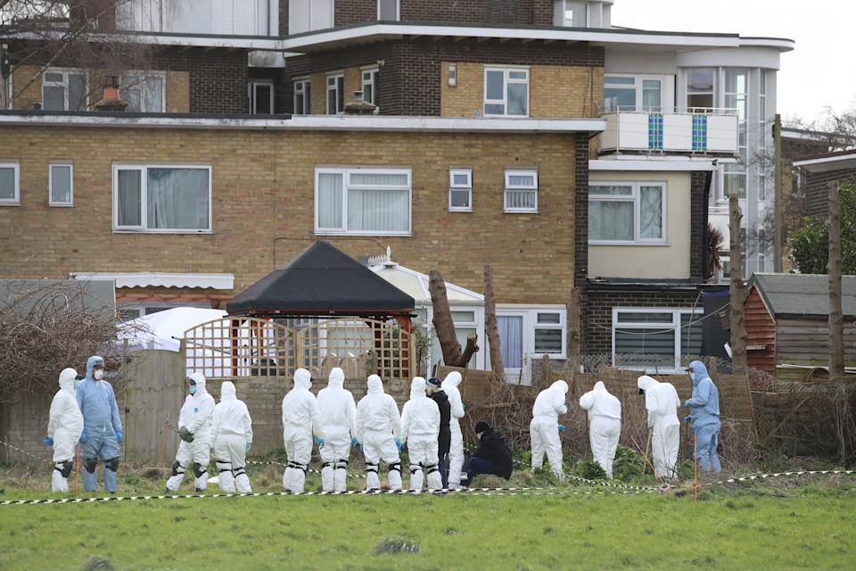 Forensic officers conduct a search behind a house in Deal, Kent, on Friday. (PA)