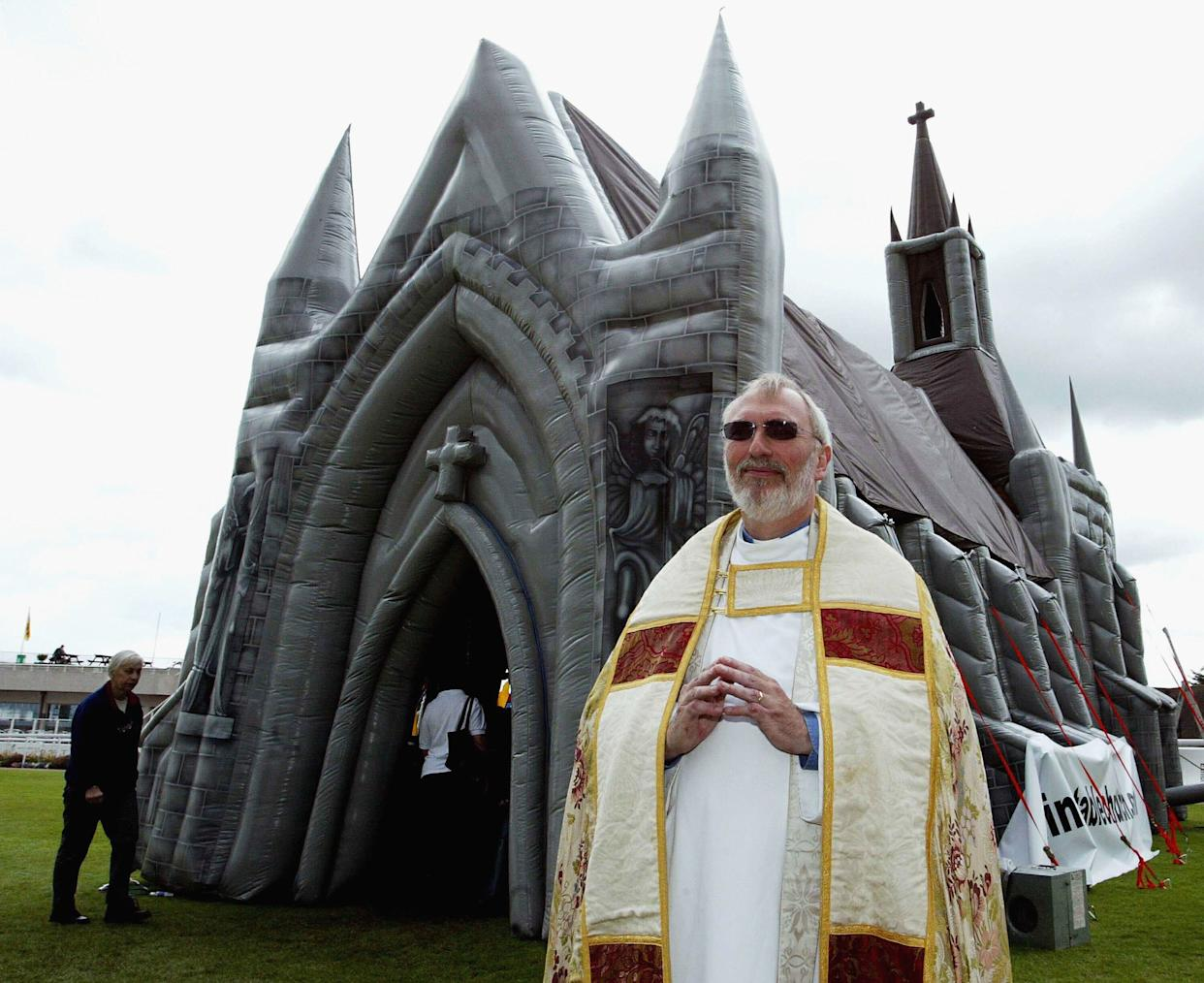 Father Michael Elfred, a church minister from Tadworth, Surrey, stands outside the world's first inflatable church, erected on May 13, 2003, in Sandown, England. The church stands 47 feet tall from floor to steeple, comes complete with inflatable organ, candles and stained glass windows, and can hold up to 60 people.