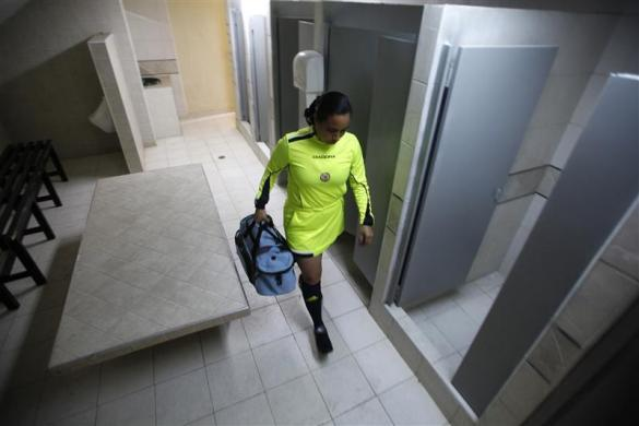 Colombian Referee Samary Rodriguez walks through a locker room on her way to a match in the second division League B championship, in Bogota, February 25, 2012.