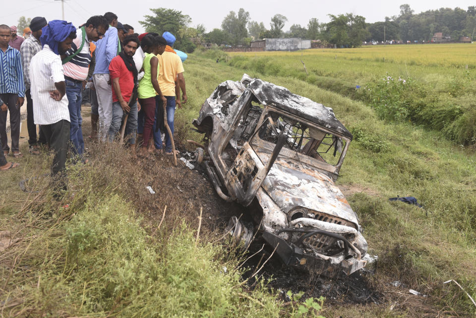 Villagers watch a burnt car which ran over and killed farmers on Sunday, at Tikonia village in Lakhimpur Kheri, Uttar Pradesh state, India, Monday, Oct. 4, 2021. Indian police on Saturday, Oct. 9, arrested the son of a junior minister in Prime Minister Narendra Modi's government as a suspect days after nine people were killed in a deadly escalation of yearlong demonstrations by tens of thousands of farmers against contentious agriculture laws in northern India, a police officer said. (AP Photo)