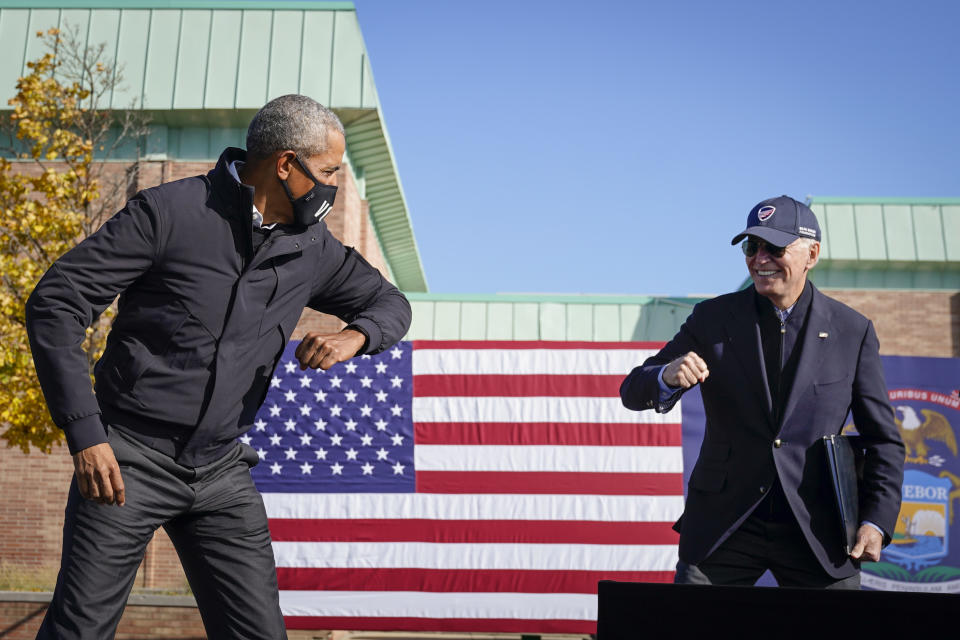 Barack Obama and Joe Biden greet each other with an elbow tap at a campaign event in Michigan on Sunday.