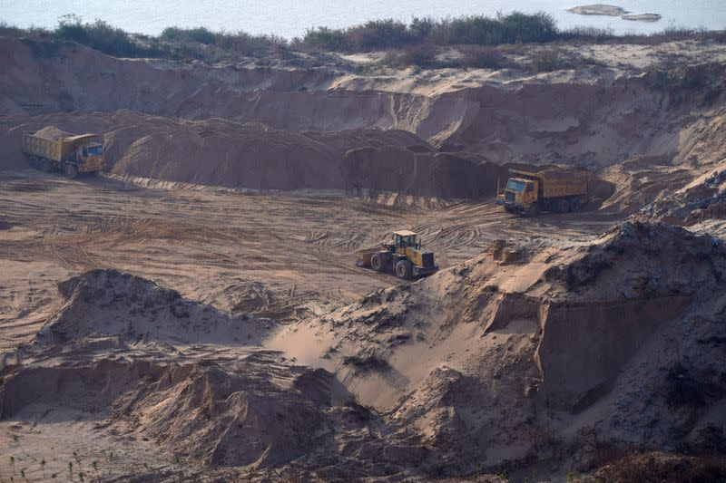 Trucks and a front loader are seen in an area cleared for sand mining on a dried lake bed of Poyang Lake in Jiujiang