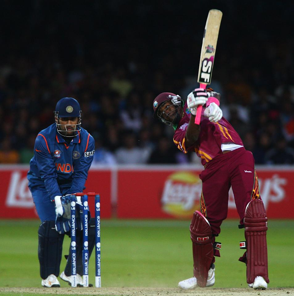 LONDON, ENGLAND - JUNE 12: Dwayne Bravo of West Indies hits out watched by Mahendra Singh Dhoni of India during the ICC World Twenty20 Super Eights match between India and West Indies at Lord's on June 12, 2009 in London, England.  (Photo by Julian Herbert/Getty Images)
