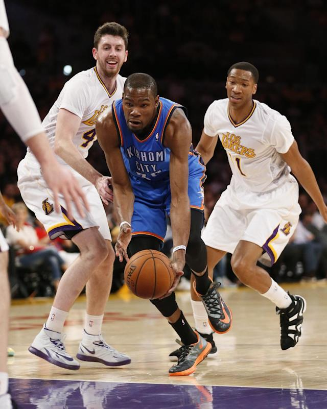 Oklahoma City Thunder small forward Kevin Durant, center, takes the ball between Los Angeles Lakers power forward Ryan Kelly, left, and small forward Wesley Johnson, right, during the first half of an NBA basketball game in Los Angeles, Sunday, March 9, 2014. (AP Photo/Danny Moloshok)