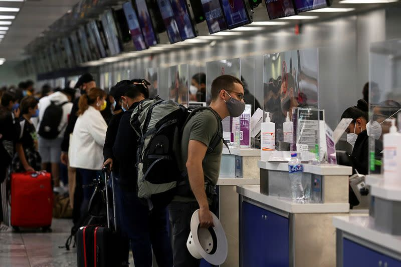 FILE PHOTO: Passengers check-in at airline counters at the Miguel Hidalgo y Costilla International Airport, operated by Mexican airport operator Grupo Aeroportuario del Pacifico (GAP), in Guadalajara