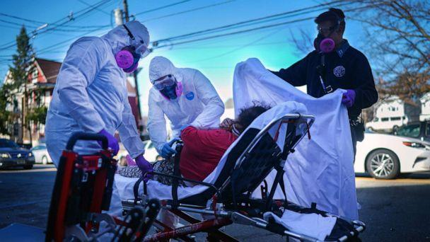 PHOTO: Fire Department emergency medical workers attend to a patient under investigation of having the coronavirus in Paterson, New York, March 24, 2020. (Chang W. Lee/The New York Times via Redux)