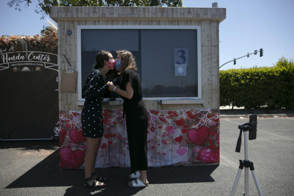 Kelly Miller, left, and Hana Stevenson kiss during their marriage service in a parking lot in Anaheim, Calif., Tuesday, May 26, 2020. Started in mid-April, the pop-up site has been serving more than 100 couples a day. (AP Photo/Jae C. Hong)
