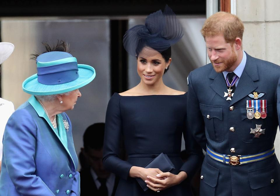 Prince Harry looks at the Queen as he stands beside Meghan Markle