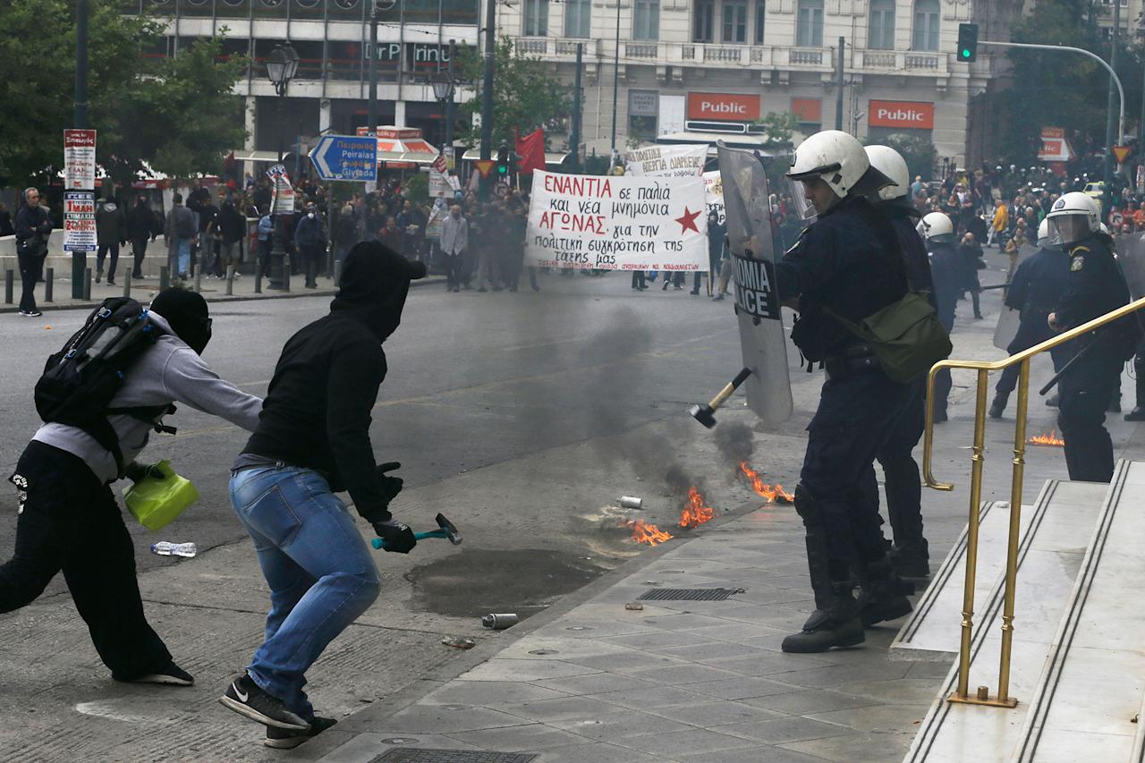 <p>A protester attacks with a hammer to a riot police officer during clashes at a nationwide general strike demonstration, in Athens Wednesday, May 17, 2017. Greek workers walked off the job across the country Wednesday for an anti-austerity general strike that was disrupting public and private sector services across the country. (AP Photo/Thanassis Stavrakis) </p>