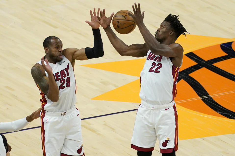 Miami Heat forward Jimmy Butler (22) and forward Andre Iguodala (28) reach for the rebound during the first half of an NBA basketball game against the Phoenix Suns, Tuesday, April 13, 2021, in Phoenix. (AP Photo/Matt York)
