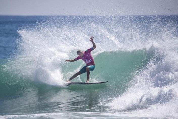Filipe Toledo does a turn on a big wave while competing against Gabriel Medina