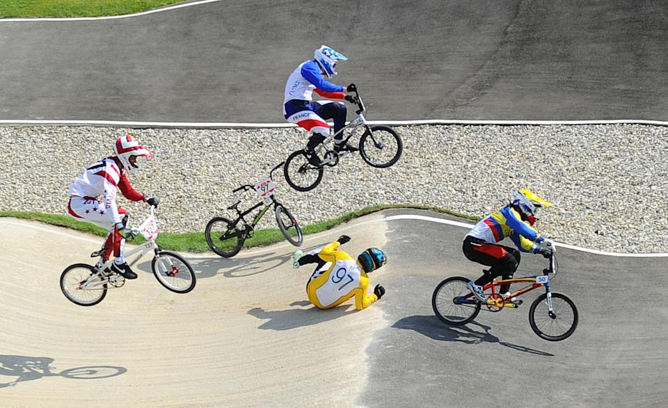 Khalen Young (AUS), #97 falls off his bike as he attempts to avoid a collision with Ea Buchely Falla (ECU), #50, and Quentin Caleyron (FRA), #14, during the men's BMX quarterfinal run in the London 2012 Olympic Games at BMX Track on August 9, 2012. (James Lang/USA TODAY Sports)